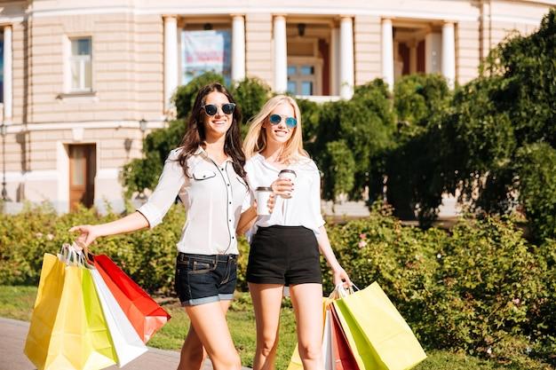 Две счастливые женщины с хозяйственными сумками гуляют на открытом воздухе