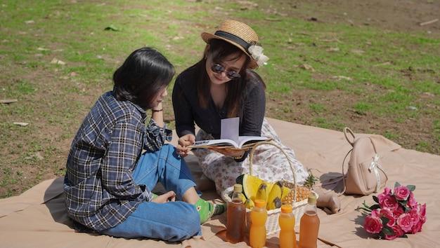 Две счастливые молодые азиатские женщины читают книгу во время отпуска у озера