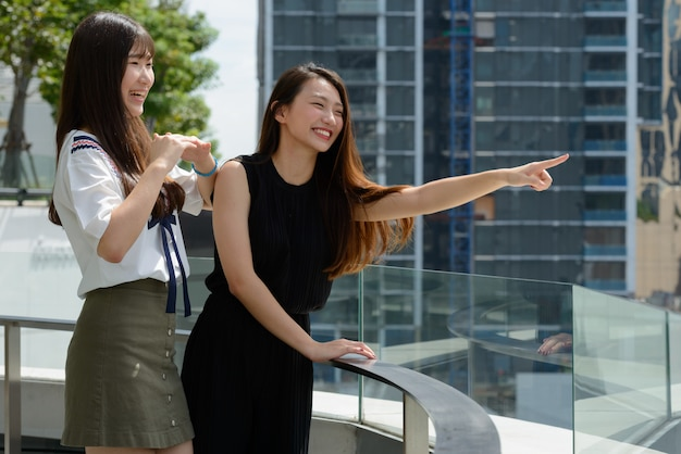 Two happy young beautiful asian teenage girls pointing at distance against view of the city