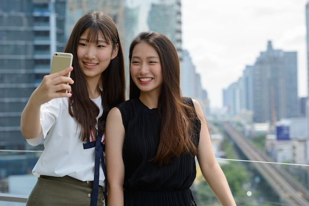 Two happy young beautiful asian teenage girls taking selfie together against view of the city