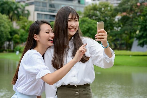 公園で一緒にselfieを取る2つの幸せな若い美しいアジアの10代女性