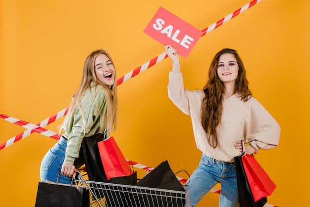Two happy young beautiful girls have sale sign and trolley with colorful shopping bags and signal tape isolated over yellow