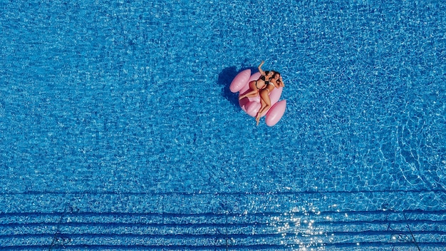 Two happy young beautiful girls with beautiful figures swim in the pool for flamingos