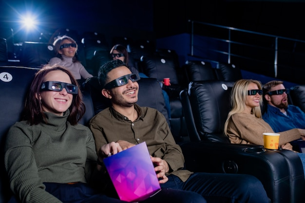 Two happy young couples sitting in comfortable armchairs in cinema, having popcorn and watching movie through 3d eyeglasses