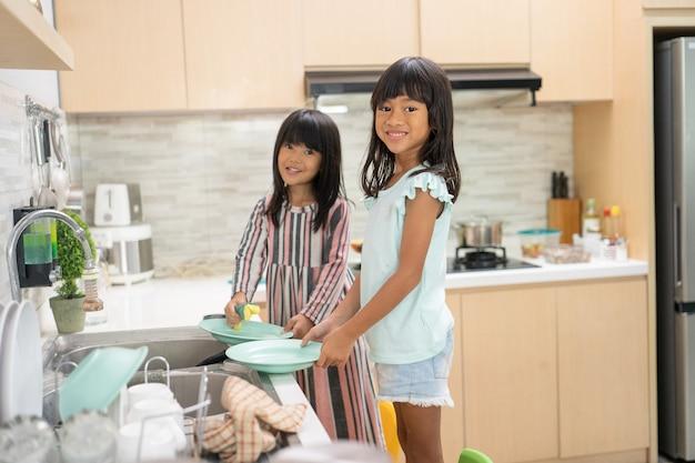 Две счастливые молодые девушки вместе моют посуду в кухонной раковине