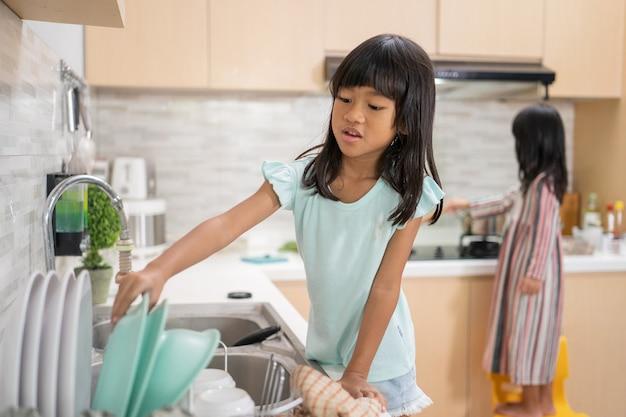 두 행복 한 어린 소녀는 부엌 싱크대에 함께 접시 세척을하고있다