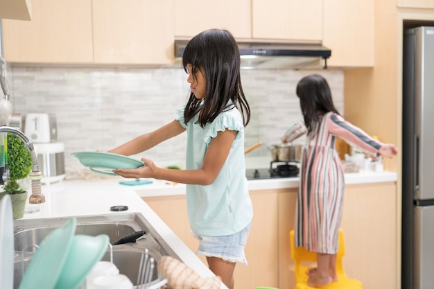 Two happy young girl are doing dish washing together in the kitchen sink