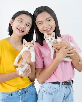 2匹の幸せな少女は2匹の猫とピンクと黄色のシャツを着ています