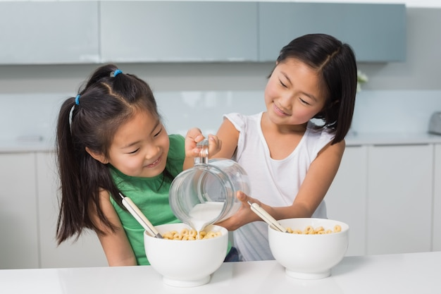 Two happy young girls pouring milk in bowl in kitchen
