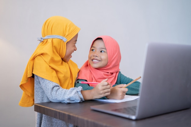 Two happy young kid studying together at home using laptop