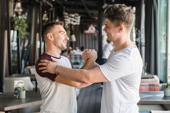 Two happy young male friends shaking hands in restaurant
