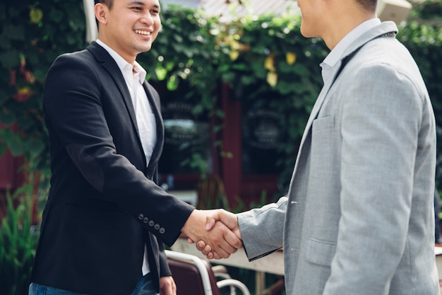 Two happy young men shaking hands