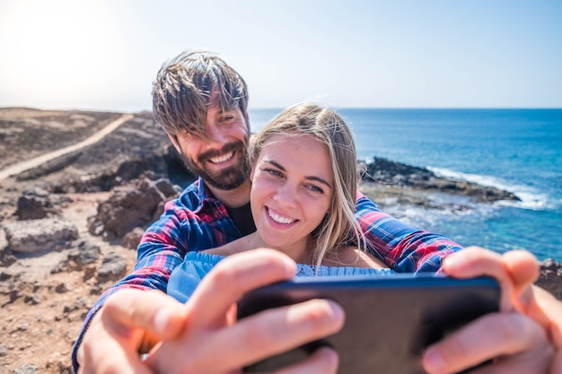 Two happy young people having fun together and taking a selfie looking at the phone - beach lifestyle and enjoying vacations and summer time with the sea or ocean at the background