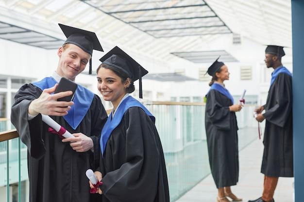 대학 내부에서 셀카를 찍는 동안 졸업 가운을 입고 스마트폰을 들고 있는 행복한 두 젊은이
