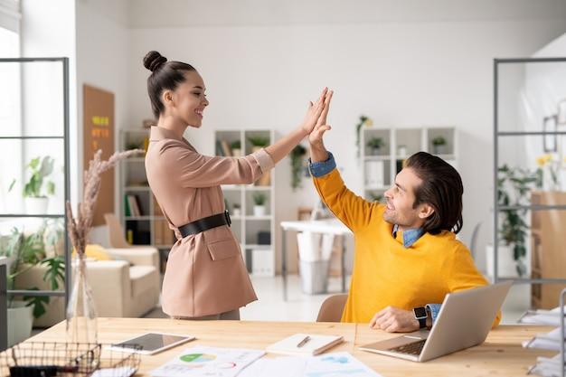 사무실 환경에서 새 프로젝트를 통해 작업을 마친 후 서로에게 하이 파이브를주는 두 행복 젊은 성공적인 동료