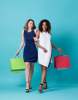 Two happy young woman hand holding shopping bag isolated over blue.
