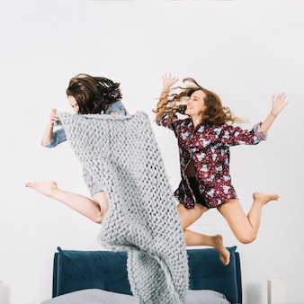 Two happy young woman jumping on bed