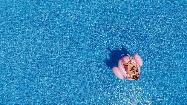 フィギュアを持った2人の幸せな若い女性がフラミンゴを求めてプールで泳ぎます。上面図。