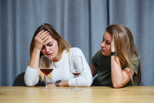 Two happy young women are friends with wine enjoying a conversation in the living room at home. girls roommate chatting at the table. european women relax talking in a cozy house.