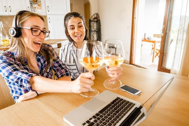 シャンパンまたは白ワイングラスで乾杯するラップトップを探してテーブルに座って自宅で2人の幸せな若い女性。社会的距離とビデオ会議技術によるオンラインでの新しい通常のお祝い
