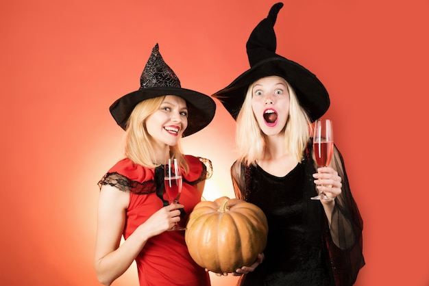 Two happy young women holding pumpkin in witch halloween costumes on party over red background