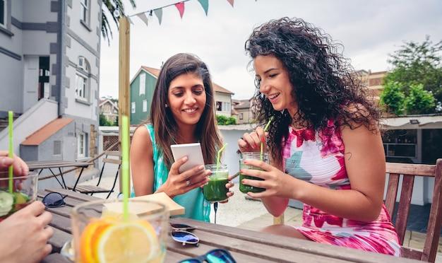 屋外で緑の野菜のスムージーを飲みながらスマートフォンを探している2人の幸せな若い女性
