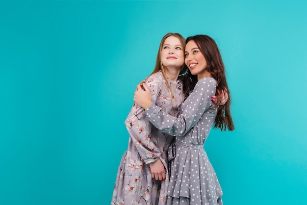 Two happy young women looking up isolated over turquoise blue background