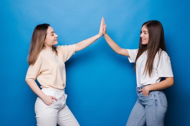 Две счастливые молодые женщины с разными волосами, дающие друг другу пять, изолированные на синей стене