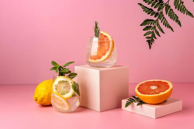 자몽과 레몬이 들어간 하드 셀처 칵테일 2 개. 그림자 고 사리와 분홍색 배경에 상쾌한 다채로운 여름 음료.