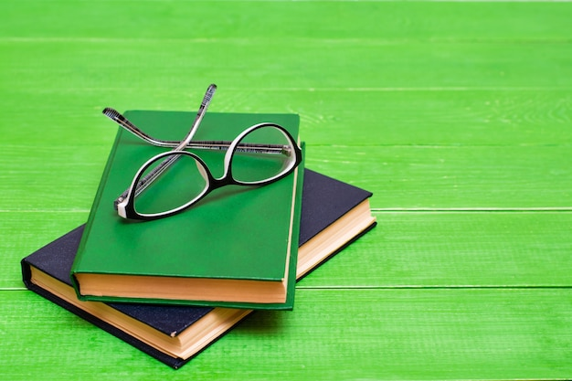 Two hardcover books and glasses  on a green wooden table. copy space