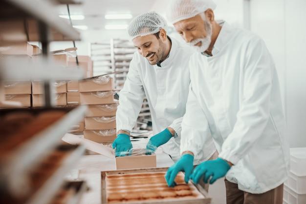 Двое трудолюбивых, преданных своему делу кавказских служащих, одетых в белую стерильную форму, собирают и упаковывают печенье в коробки. интерьер пищевого завода.