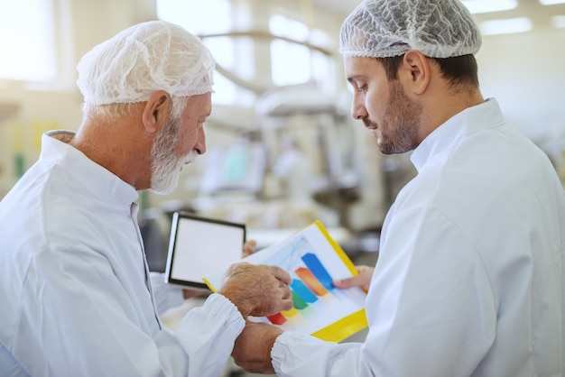 Two hardworking supervisors checking statistics while standing in food plant. older one holding tablet. both are dressed in white sterile uniforms.