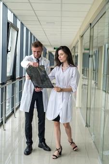 Два медицинских специалиста смотрят на рентгеновское изображение, мрт головного мозга пациента для диагностики и лечения в больнице