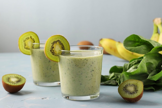 Two healthy detox smoothie kiwi, banana, spinach in glasses on light blue background with fresh ingredients