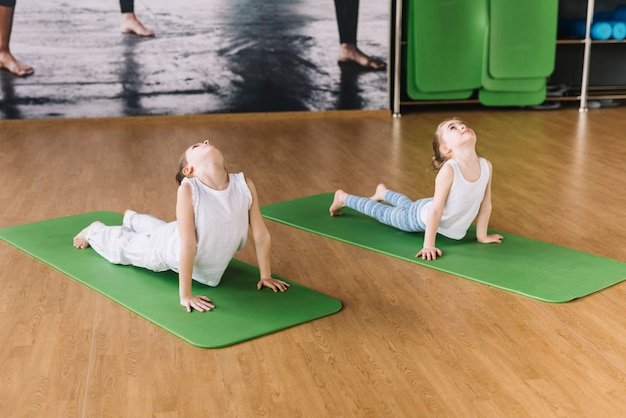 Two healthy girl exercising on green mat over wooden desk