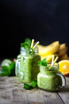 ガラスの瓶と材料にほうれん草、バナナ、オレンジ、ミントが入った2つの健康的なグリーンスムージー。デトックス、ダイエット、健康、ベジタリアン料理のコンセプト。コピースペース