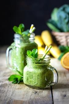 Два здоровых зеленых коктейля со шпинатом, бананом, апельсином и мятой в стеклянной банке и ингредиентами. детокс, диета, концепция здорового, вегетарианского питания.