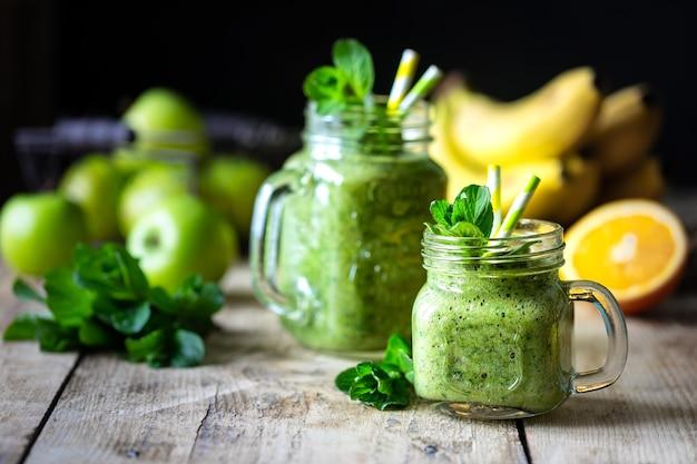 Два здоровых зеленых коктейля со шпинатом, бананом, апельсином, яблоком, киви и мятой в стеклянной банке и ингредиентами. детокс, диета, концепция здорового, вегетарианского питания.