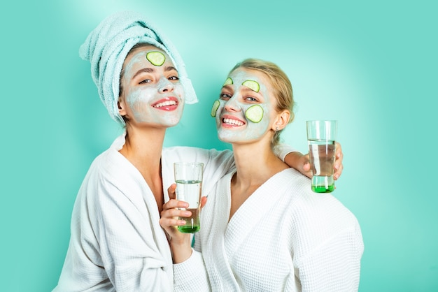 Two healthy natural girls smile and drink water moisturizing clay mud mask and slices of cucumber at...