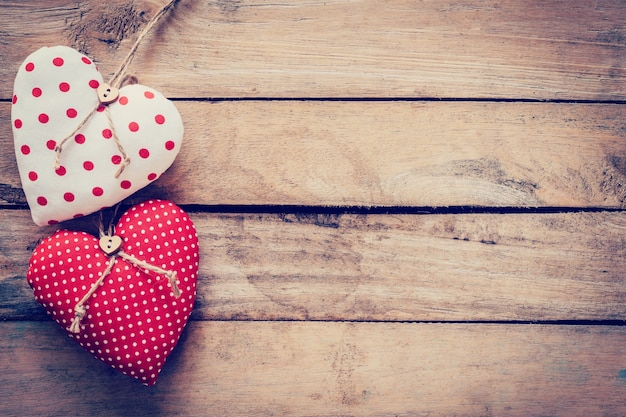 Two heart fabric on wooden table background.