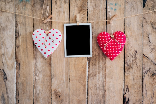 Two heart and photo frame hanging on clothesline rope with wooden background.