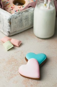 Two heart shape cookies on beige background