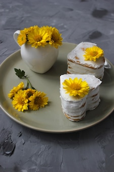 Two heart shape honey cakes with decor from yellow flowers on ceramic plate
