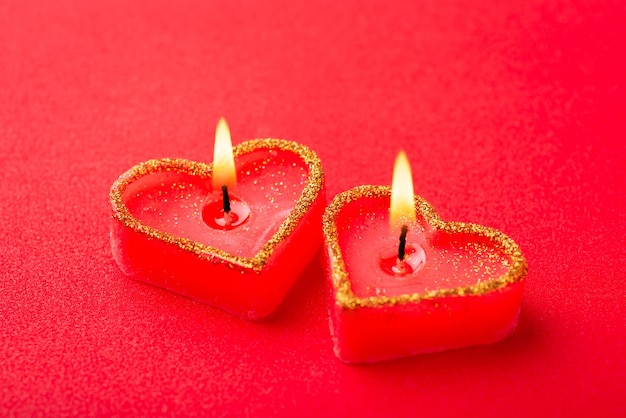 Two heart shaped burning candles close up