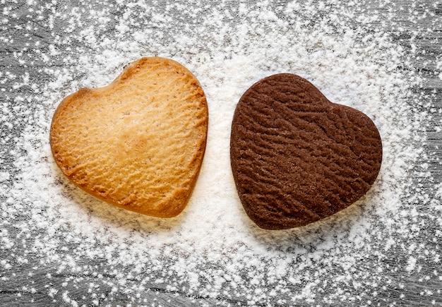 灰色の木製の背景に2つのハート型のクッキー。焼きバターとチョコレートクッキー。バレンタインデーのコンセプト。上面図。