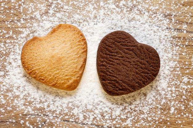 木製の背景に2つのハート型のクッキー。焼きバターとチョコレートクッキー。バレンタインデーのコンセプト。上面図。
