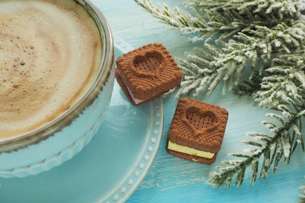 Two heart-shaped cookies on a saucer near a cup of coffee. spruce artificial branch.