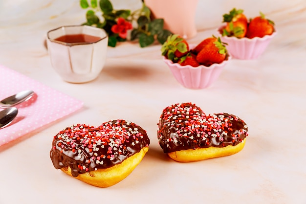 Two heart shaped donuts with chocolate glaze and pink, red sprinkles on a platet with strawberry.
