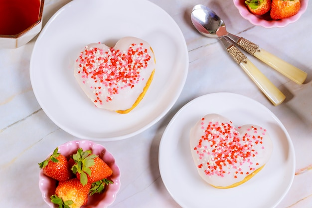 Two heart shaped donuts with white glaze and pink, red sprinkles on a platet with strawberry.