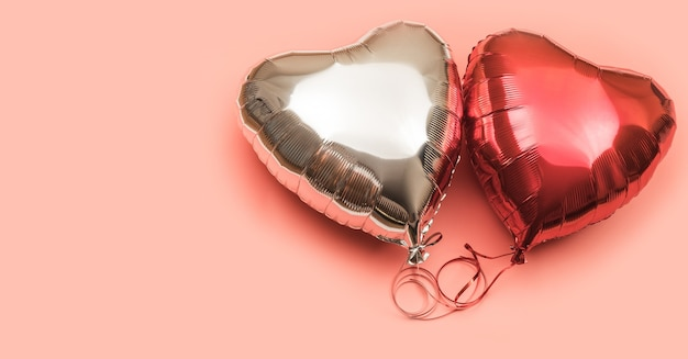 Два воздушных шара из фольги в форме сердца на розовом фоне с местом для текста. красные и серебряные шары на светлом фоне.